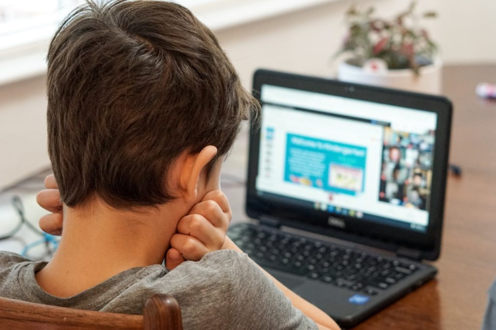 Boy online learning at laptop
